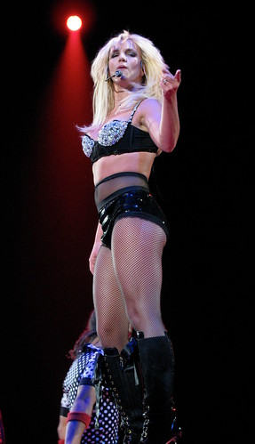 Britney Spears Concert - You Want A Piece Of Me?: Britney Spears, a young female artist, on stage in black latex and fishnets.