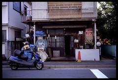Just something quite normal (gullevek) Tags: street door plants building window sign japan wall writing geotagged iso100 tokyo cone scooter motorcycle 日本 東京 housebuilding 月島 fujivelvia100f 中央区 fujigw690iii geo:lat=35662847 ebcfujinon90mmf35 geo:lon=139778499