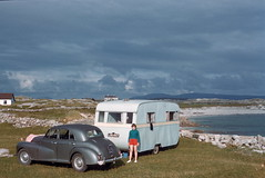 Car and caravan, Roundstone, Co. Galway (1959) (The Douglas Campbell Show) Tags: house galway rock landscape person coast vehicle ie roundstone irishrepublic