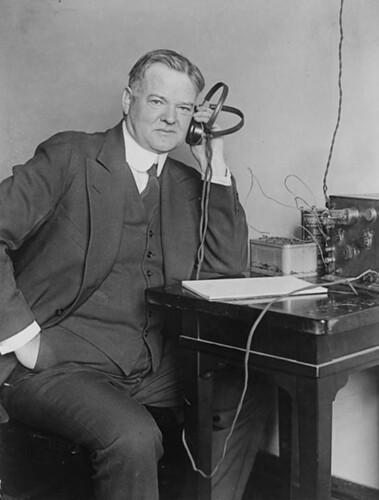 Herbert Hoover, three-quarter length portrait, seated, facing slightly right, listening to radio.
