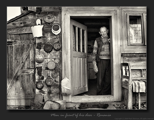 Man In Front Of His Door by M. Sherman.
