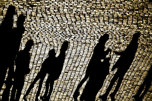 shadows of people on cobblestones