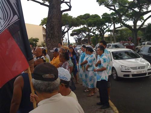 出勤するタヒチ市民の車やバイクが、裁判所の門が開くのを待つ元労働者と支援者たちを見ながら通り過ぎて行く。元労働者たちによると、今ではポリネシア住民の95%が元核実験労働者の運動に賛成しているという。