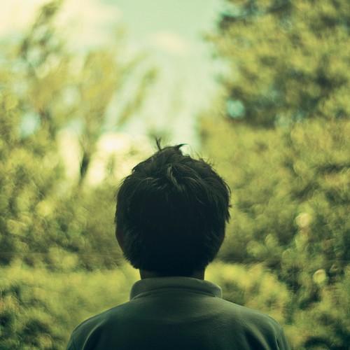 Fotografía de un chico moreno de espaldas con follaje al fondo