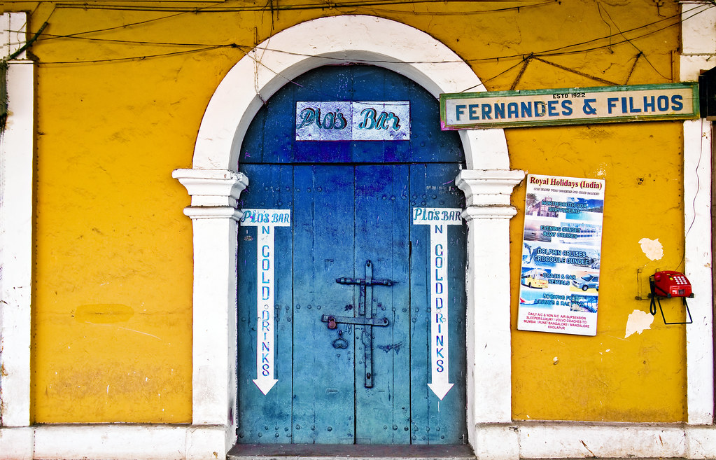 Pio's Bar With a Barred Doorway in Blue framed in Yellow walls of Panjim, Goa India. Surprising thing is that it is closed !