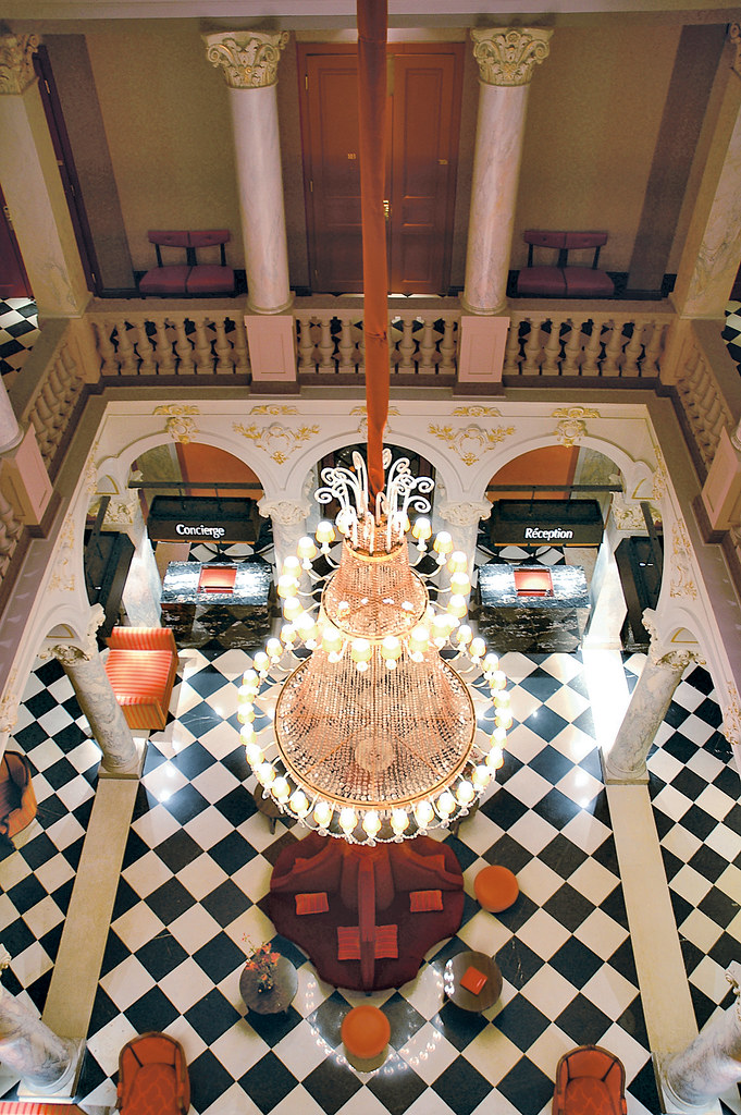 Lobby and hall, tiles in checkboard black and white with magnificent Chandelier at the Hotel de la Paix Geneva in Switzerland