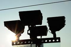 (Olivier H) Tags: blue sky sun black lamp yellow jaune lampe soleil wire noir projector outdoor cable bleu ciel lightpole contrejour lampadaire slihouette projecteur exterieur