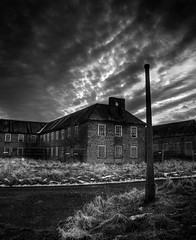 Driffield Exterior (Matthew Kelly) Tags: road uk light england sky urban white snow black building rot abandoned ice overgrown monochrome grass clouds canon outside mono ruins exterior post gates matthew decay yorkshire great east kelly fencing derelict base hdr boarding britian dereliction raf upon ue driffield composit staton exposures urbex wolds photomatix 400d explorarion