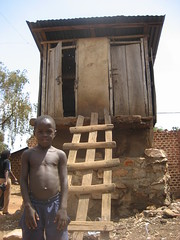 Boy in front of typical Pit latrine in Kampala slums