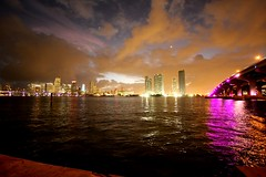 Miami Skyline - dusk (The Korky) Tags: bridge blue sunset orange water skyline night clouds canon reflections lights downtown all purple florida dusk aaron airplanes jackson rights efs 1022mm reserved 40d abigfave aaronjackson anawesomeshot theunforgettablepictures picturefantastic flickrslegend 5flickrfavs internationalgeographic miammi reflectyourworld micarttttworldphotographyawards micartttt vicariousphotography vicariousphotographycom vicariousphotographygmailcom wwwvicariousphotographycomcopyright
