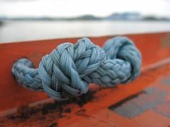 Blue knot (peggyhr) Tags: ocean blue brazil orange mountains closeup bay iron paint dof rope knot pr carferry peggyhr guaratubatocaiob