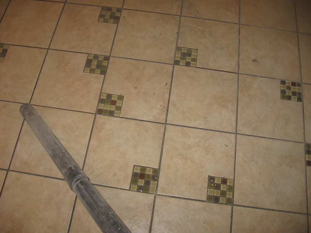 the newly tiled floor in the men's bathroom