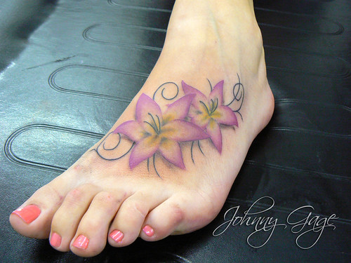 tattoos of lilies on feet. lily and florishes on foot