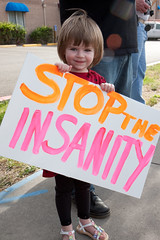 cute little girl holding sign saying 'stop the insanity'