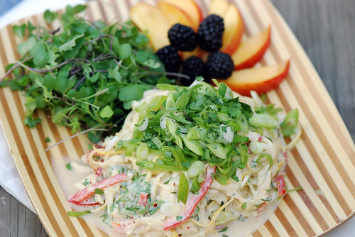 Raw squash noodles and veggies with spicy tahini sauce and fresh herbs