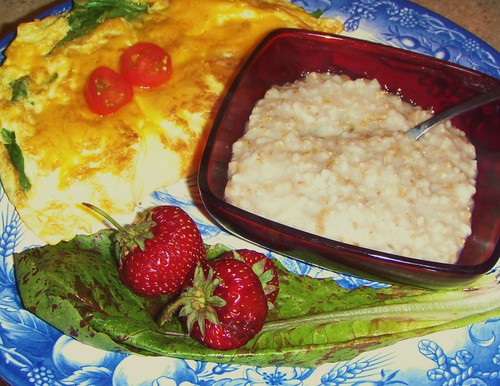 omelet with tomatoes on top and bowl with grits and two strawberries