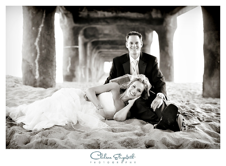 bride and groom laying down in the sand underneath the pier at the beach