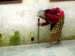 Elder Nepalese woman doing circumambulations of the Boudha Stupa, bent with arthritis, Boudha, Kathmandu, Nepal