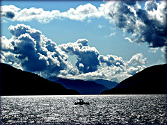 between sky and sea ...............             is where I love to be (calamityjan2008) Tags: ocean blue sky sun white black mountains clouds waves fluffy boating inlet soe tup 3colours fluffyclouds sunonwater bej abigfave theunforgettablepictures platinumheartaward fbdg worldwidelandscapes 100commentgroup