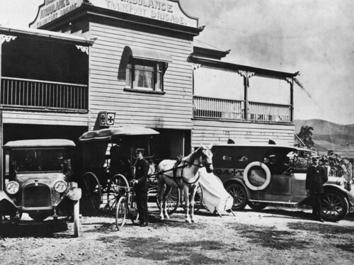 Horse drawn cart with two motor vehicles parked outside the Ambulance Transport Brigade building at Mount Morgan, ca.1921