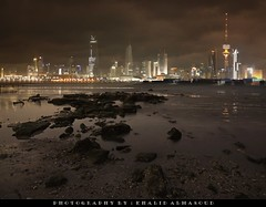 Kuwait city at night in low tide - 26 Mar 2009 (khalid almasoud) Tags: city tower skyline night canon buildings eos rocks photographer cloudy tide low kuwait liberation khalid      50d   almasoud