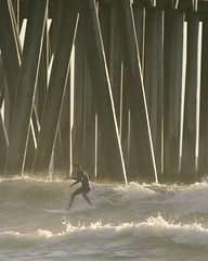 The Concrete Forest (ScottS101) Tags: ocean ca winter sunset male beach youth fun pier surf waves pacific surfer wave playa teen surfboard pilings athlete olas huntingtonbeach hombre hb wetsuit homme chavo surfista