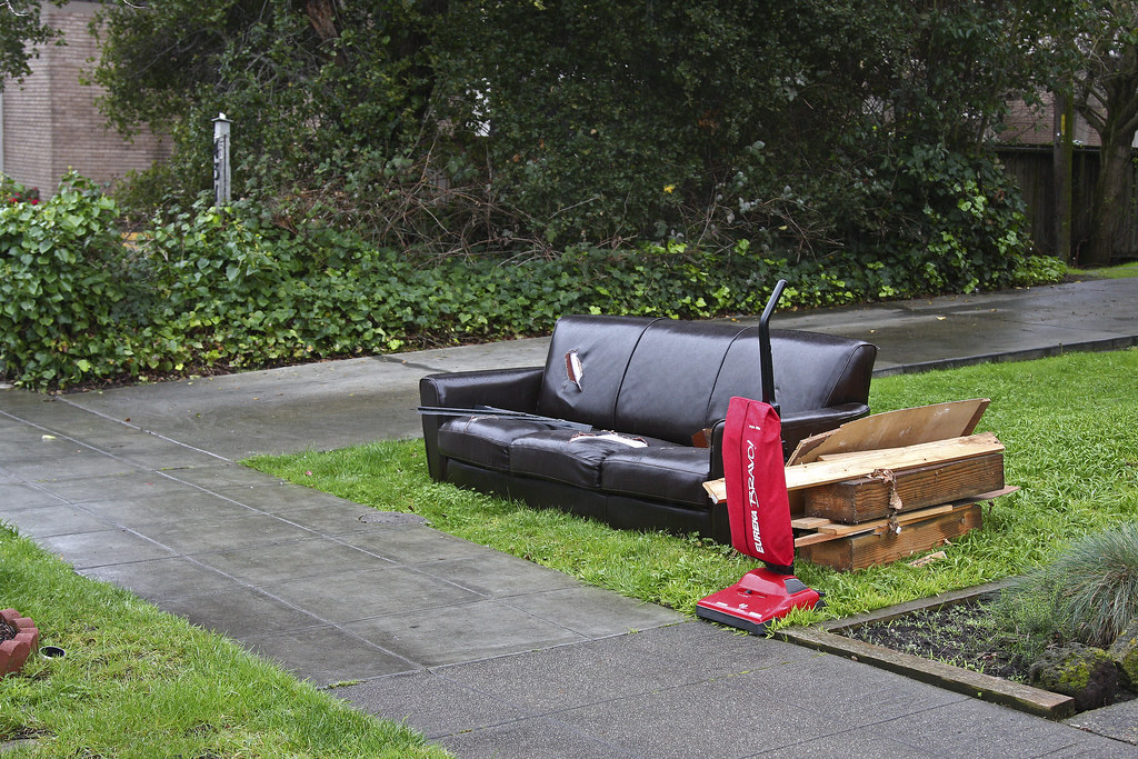 Abandoned sofa and vacuum cleaner