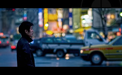 Alone in Shibuya; Tokyo, Japan (Alfie | Japanorama) Tags: street city urban man streets cars car japan night asian japanese lights evening nikon waiting asia neon alone crossing bokeh candid widescreen taxi watching shibuya single cinematic afterdark d300 nikkor85mmf14afd