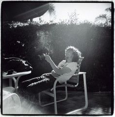 Charlie Moonheart - By the Pool (Claire Marie Vogel) Tags: camera light boy portrait people sun moon white man black film beach analog hair square relax photography photo claire holga lomo lomography weed san francisco sitting heart image 5 cigarette smoke smoking plastic charlie curly photograph portraiture sit flare medium format laguna seated vogel 5x5 moonheart moothart
