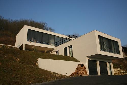 une maison moderne de trois niveaux, accrochée au plus près de la pente.
