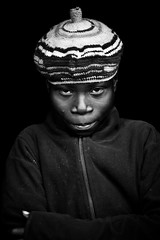 E Y E S  - DR CONGO - (C.Stramba-Badiali) Tags: travel light boy portrait people blackandwhite face look blackbackground canon pose dark person eyes noiretblanc lumire african culture 85mm shy yeux blackpeople congo tradition bonnet ethnic humanbeing humanitarian oneperson drc bunia visage garon regard zaire rdc drcongo blackskin displacedperson lookingatcamera centralafrica ethno africanchildren gety ethnie ituri peaunoire timidit afriquecentrale lendu 5dmkii regardcamra forgottenconflict strambabadiali lenduboy