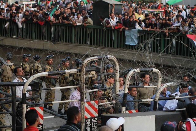 قوات الجيش مرتدية قناع الغاز من قبل تفرثق المظاهرة بساعات
