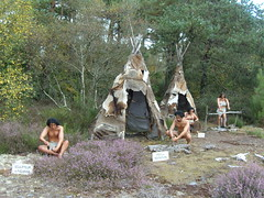 Scene of typical activities in a neolithic camp site, carving figurines, making fire, gutting and cooking animals