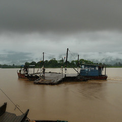 Ferry crossing the mighty Mekong river (Bn) Tags: topf50 sinister monsoon laos raining route13 darkclouds rainyseason mekongriver champasak wetseason 50faves ferrycrossing riverscene champasakprovince rainymonsoon sinisterscene mekongferry wildestrainyseason awoodenplatform fullyloadedferry crossingthemekong ferryatchampasak travelingisatleasthalfthefun largeraft raininginthemountains stormabovethemountains lowcloudsinthemountians