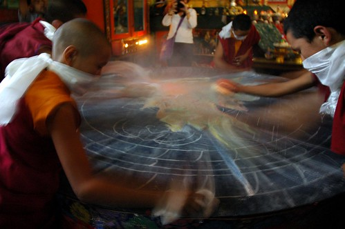 Dust from Hevajra Empowerment rises above the work as young monks clear off the mandala, Tharlam Monastery of Tibetan Buddhism, Boudha, Kathmandu, Nepal