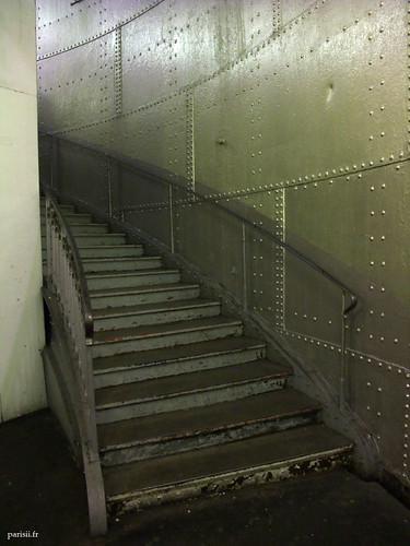 Escaliers en métal, montant le long des plaques rivetées