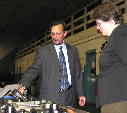 Aztec Manufacturing President and CEO Greg Lopez (right) shows some of the precision-cut auto parts made by his company to Agriculture Deputy Secretary Kathleen Merrigan.