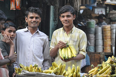 Banana Men, Kolkata India (Laura Dunn-Mark) Tags: street travel people india men smile yellow chinatown market expression offer bananas surprise bunch shock vendor indians bazaar cart 2008 kolkata salesmen calcutta westbengal lauradunnmark tiretta