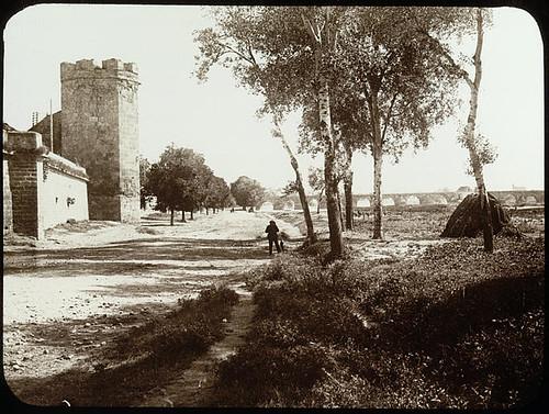 Lestrange. Tour et remparts, arbres, aqueduc à larrière-plan, photographe en cours de prise de vue (supposé).