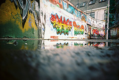 Lomo 0725 (ukaaa) Tags: street urban reflection film wall analog 35mm puddle graffiti lomo lca lomography dof belgium kodak bokeh low belgi ground tags depthoffield negative pointandshoot analogue 135 portra ghent gent legal portra160vc passway ratseyeview werregarenstraat