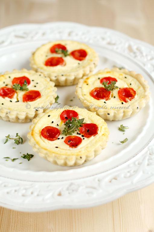 Tartellette ai semi di nigella, pomodorini e formaggi