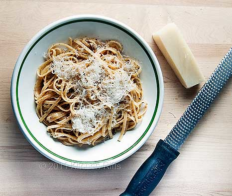 Pasta Cacio e Pepe (Romano cheese and black pepper) in bowl with hunk of Romano and grater