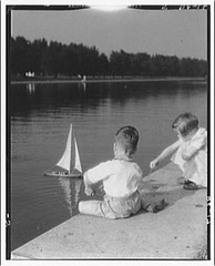 Boy and girl sailing their sailboat at the reflecting pool Washington DC USA Photographer Theodor Horydczak 1890-1970 (oldsailro) Tags: park old boy sea summer people sun lake playing beach boys water pool girl sunshine youth sailboat race vintage children fun toy boat miniature wooden dc washington pond model waves sailing ship child time yacht antique group boom mat regatta hull spectators watercraft adolescence keel fashioned choldren