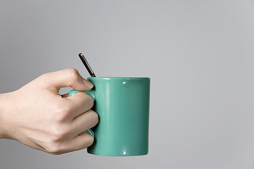 woman hand holding a tea cup with a spoon close up a photo on