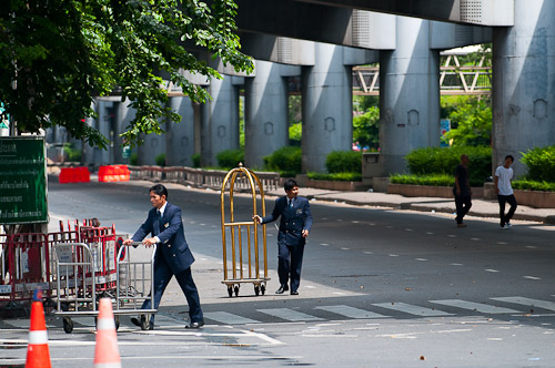 Employees of the Dusit Thani helping to evacuate guests on the empty streets of Bangkok