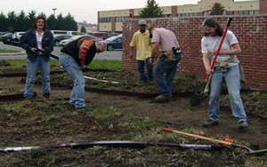 NRCS employees dig out paths and install borders and landscape fabric.