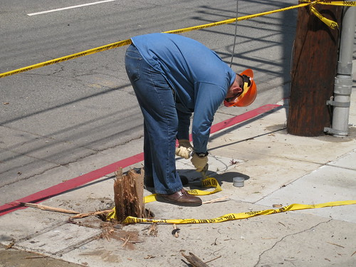 worker cleaning up mess around downed utility pole