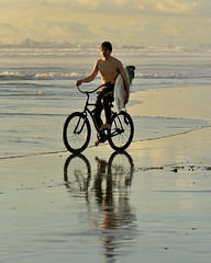 Beach Cruiser (ScottS101) Tags: california winter light sunset male beach wet bicycle youth reflections golden pier surf surfer young warmth teen surfboard pilings february huntingtonbeach 2009 cruiser hb wetsuit homme wetsand surfista beachcruiser homebre