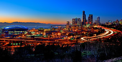 Seattle Alive at Sunset (Surrealize) Tags: seattle city longexposure sunset motion cars skyline buildings lights moving nikon neon traffic pugetsound seahawks headlight qwestfield hdr taillight smithtower olympicmountains columbiatower d700 surrealize