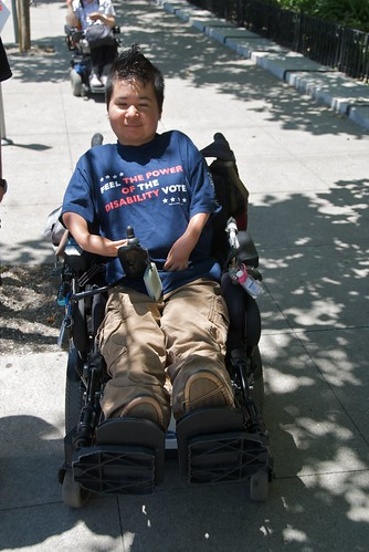 A person in a powerchair wearing a shirt that says 'feel the power of the disability vote.' Photo taken at a protest in California.